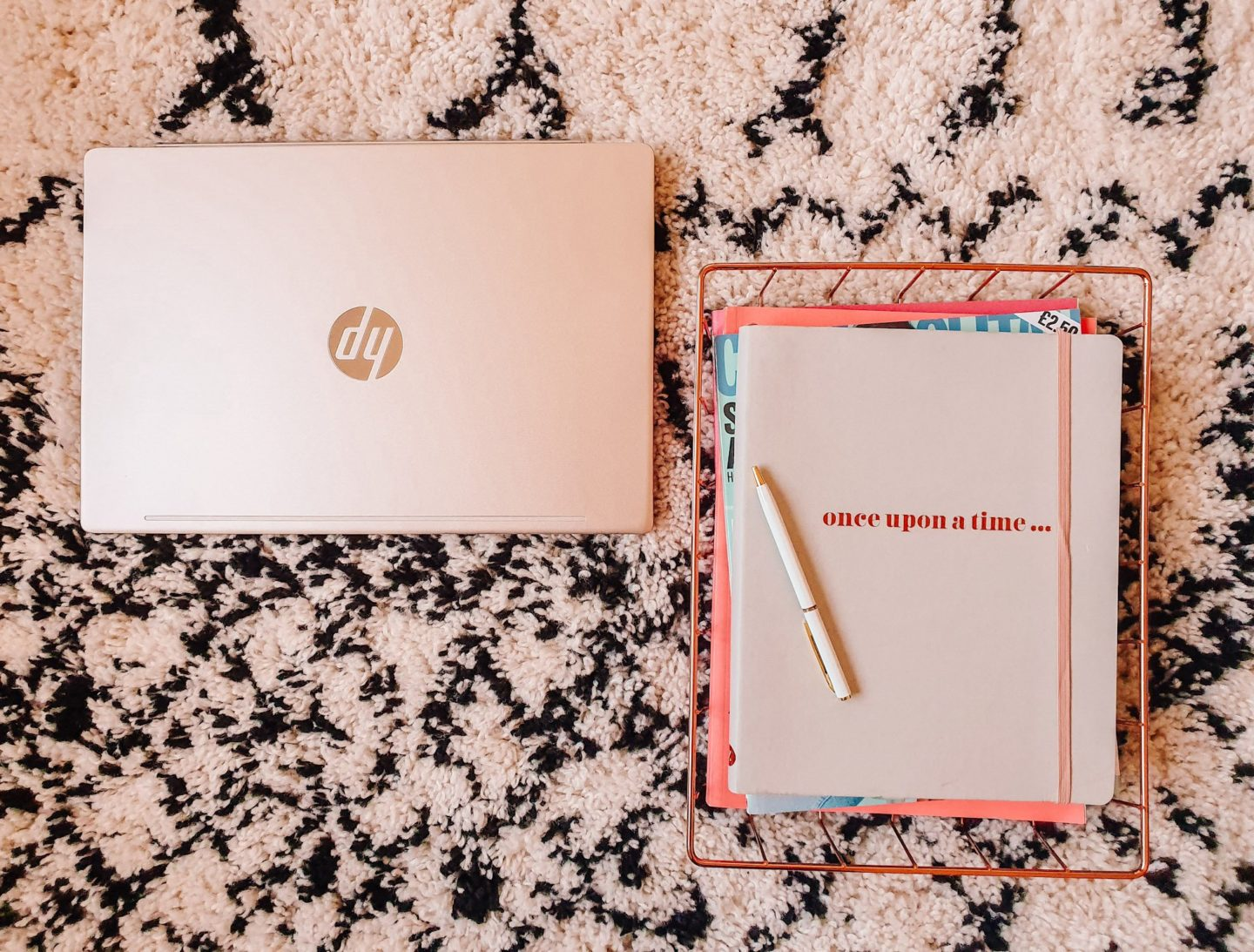 "A closed laptop and grey notebook that says ""once upon a time"" with a white pen resting on it on a La Redoute black and white rug"
