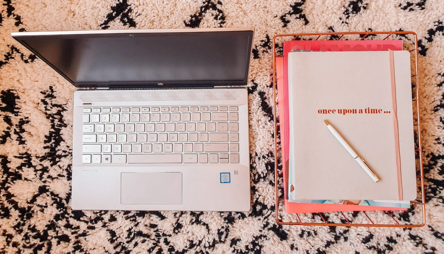 "An open laptop and grey notebook that says ""once upon a time"" with a white pen resting on it on a La Redoute black and white rug"