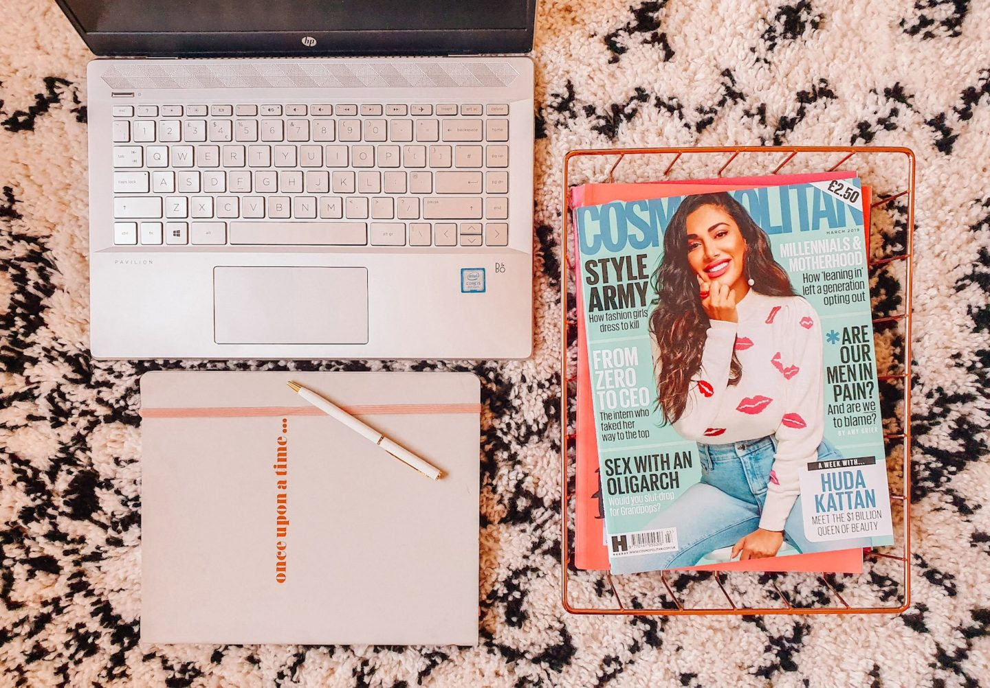 "A laptop and grey notebook that says ""once upon a time"" with a white pen resting on it and a copper wired tray with a copy of Cosmopolitan magazine with Huda Beauty on the front on a La Redoute black and white rug"