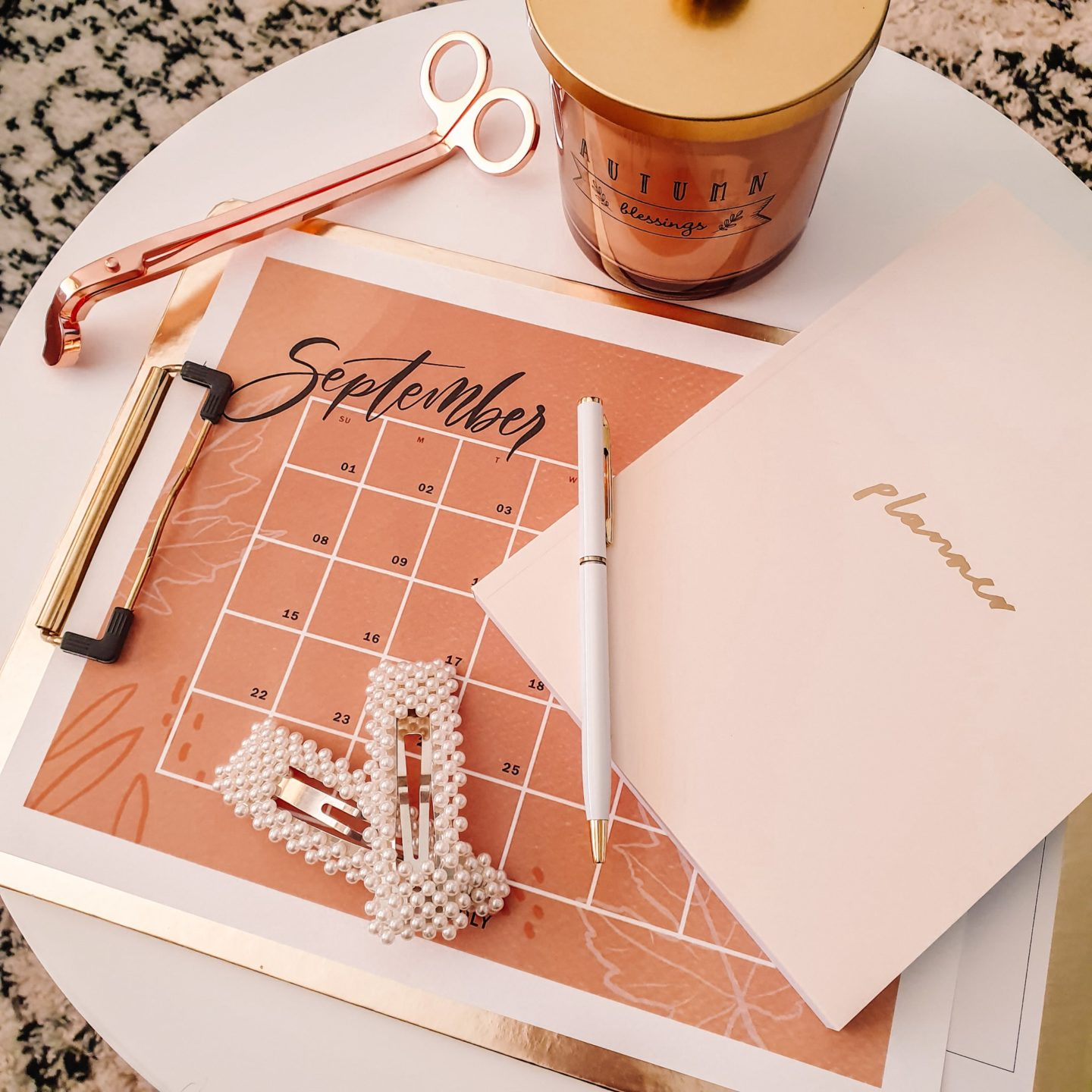 Autumn Candle and print out September month on a gold clipboard with a pink planner notebook, white pen and rose gold candle wick trimmer on a white round table